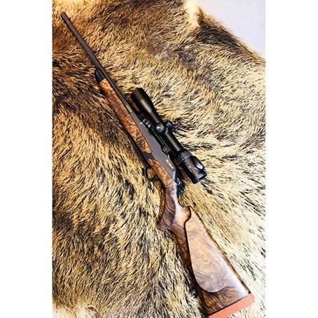 Jagdgewehr mit Optik auf Wildschweinfell
